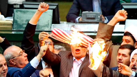Iranian lawmakers burn two pieces of papers representing the U.S. flag and the nuclear deal as they chant slogans against the U.S. at the parliament in Tehran, Iran, Wednesday, May 9, 2018. Iranian lawmakers have set a paper U.S. flag ablaze at parliament after President Donald Trump