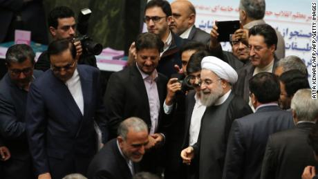 "TOPSHOT - Iranian President Hassan Rouhani (C) arrives to parliament ahead of presenting the proposed annual budget in the capital Tehran, on January 17, 2016, after sanctions were lifted under Tehran's nuclear deal with world powers. Iran has ""opened a new chapter"" in its ties with the world, President Hassan Rouhani said, hours after sanctions were lifted under its historic nuclear deal with global powers. A day earlier the UN's atomic watchdog confirmed that Iran has complied with its obligations under the July deal and the United States and European Union announced it was lifting the sanctions that have for years crippled the country's economy.   / AFP / ATTA KENARE        (Photo credit should read ATTA KENARE/AFP/Getty Images)"
