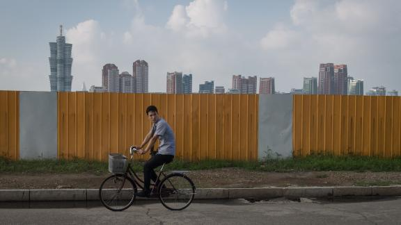 TOPSHOT - A photo taken on July 24, 2017 shows a man cycling along a street before the skyline of Pyongyang. / AFP PHOTO / Ed JONES        (Photo credit should read ED JONES/AFP/Getty Images)