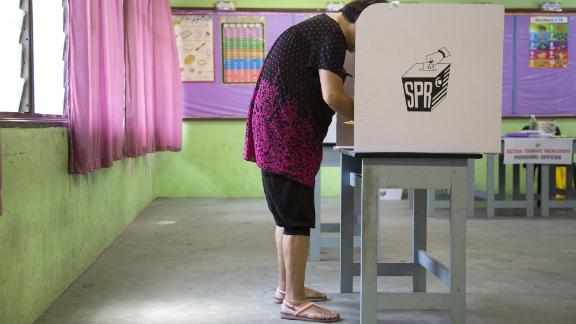 A voter wearing shorts and flip-flops fills out a ballot at a polling station in the Desa Petaling area of Kuala Lumpur, Malaysia, on Wednesday. Some voters were turned away by officials citing dress restrictions -- despite assurances that would not happen.