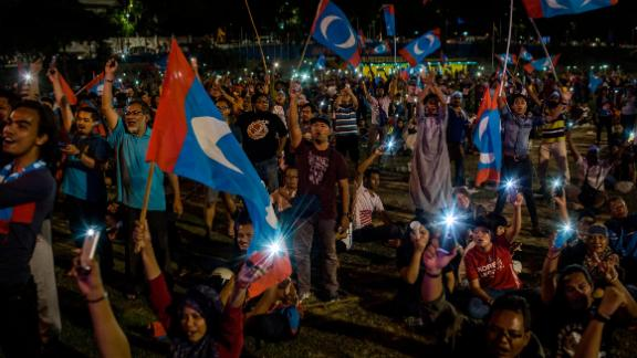 Supporters of Mahathir Mohamad cheer as they watch live televised result announcement in Kuala Lumpur.