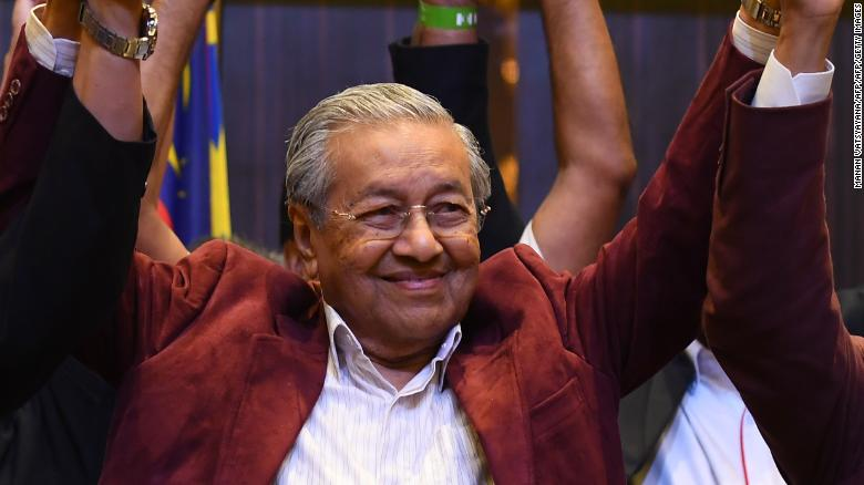 Mahathir Mohamad celebrates with his coalition leaders during a press conference in Kuala Lumpur on May 10.