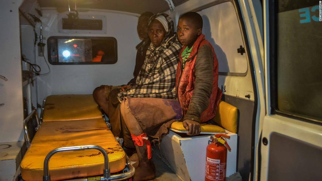 Local residents wait inside an ambulance.