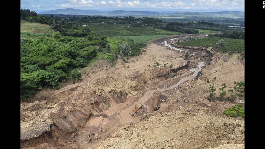 "People survey the area of erosion caused by the flood. According to Lee Kinyanjui, the governor of Nakuru County, those affected by the dam are ""mostly workers and small-scale farmers."""