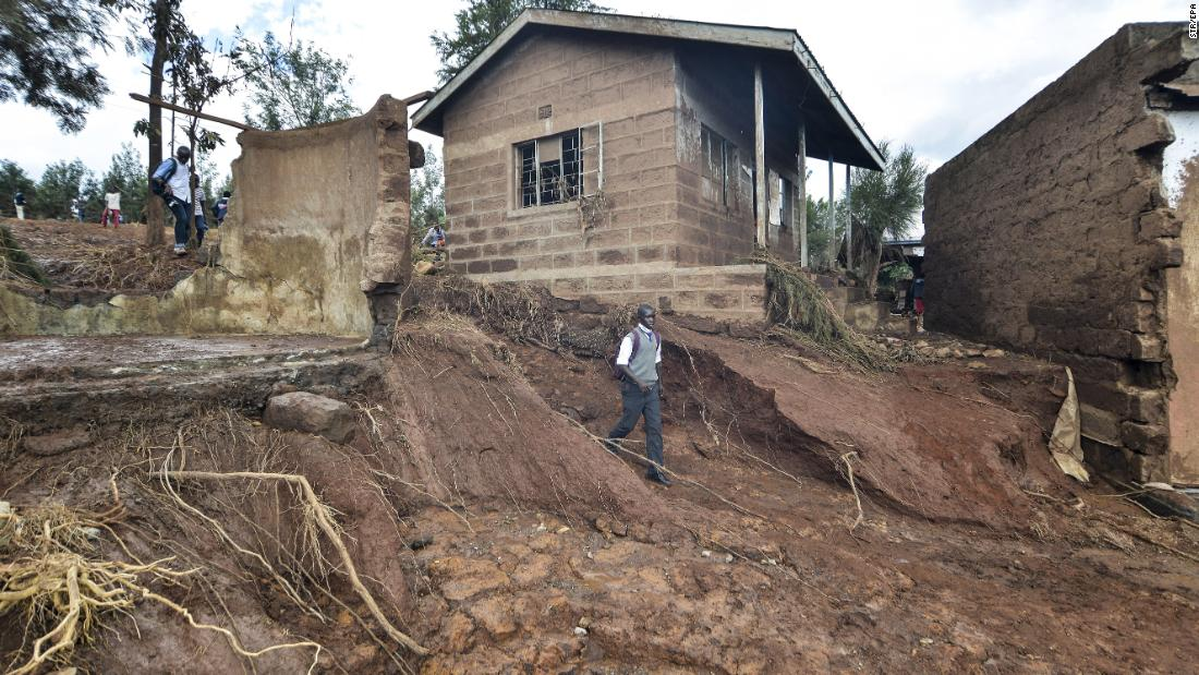 A boy walks down a steep hillside that was created when water from the breach swept soil away.