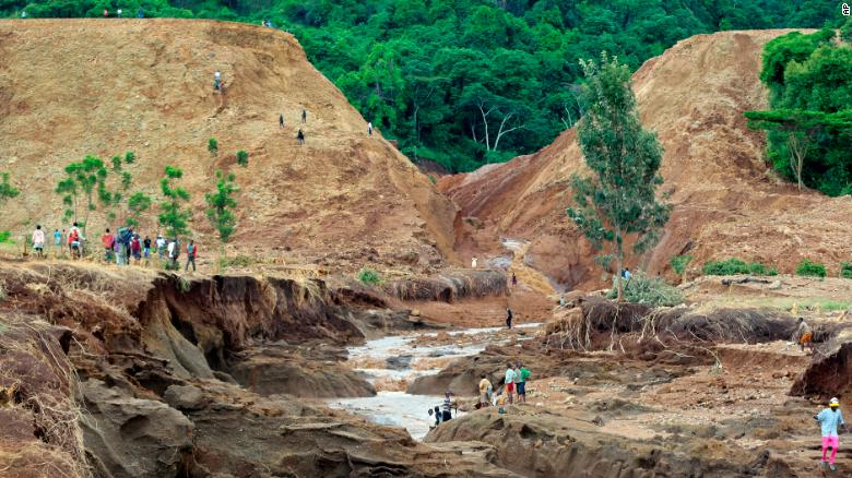 People gather in front of the broken banks of the Patel dam in Kenya's Rift Valley on Thursday, May 10. The Kenya Red Cross Society estimated that up to 500 families have been affected by the disaster.