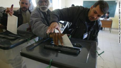 An official guides the hand of blind man Jawwad Shkeir, 56, as he cast his vote on 30 January 2005, in the southern holy city of Najaf. The elections were Iraqs first full vote since Saddam Hussein was routed from power in 2003.