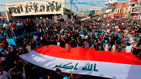Followers of Shiite cleric Muqtada al-Sadr carry a huge Iraqi flag as they take part in a campaign rally in Baghdad on May 4.