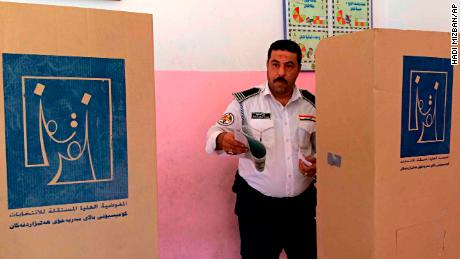 An Iraqi traffic policeman prepares to cast his vote at a polling center in Baghdad, Iraq, Thursday, May 10, 2018. Soldiers and security forces cast ballots ahead of parliamentary elections. (AP Photo/Hadi Mizban)