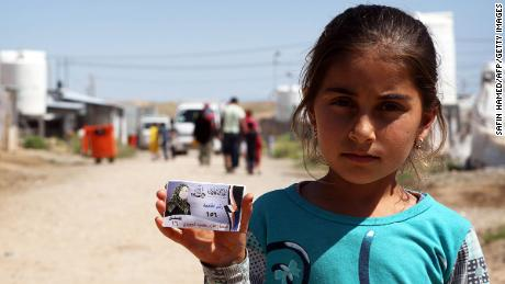 A displaced Iraqi girl from the former embattled city of Mosul poses for a photo holding an election campaign card, at the Hasan Sham camp, some 40 kilometres east of Arbil in northern Iraq, on May 1, 2018, two weeks before Iraqis are set to vote in the parliamentary elections. (Photo by SAFIN HAMED / AFP)        (Photo credit should read SAFIN HAMED/AFP/Getty Images)