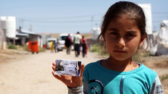A displaced Iraqi girl holds an election campaign card, at the Hasan Sham camp in northern Iraq, in May 2018.