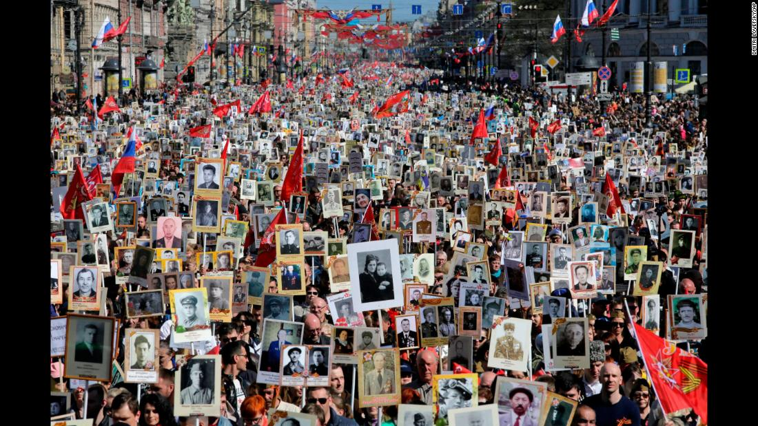 "People in St. Petersburg, Russia, carry portraits of their ancestors, World War II veterans, during an ""Immortal Regiment"" march on Wednesday, May 9. The annual march pays tribute to those who helped defeat the Nazis 73 years ago."