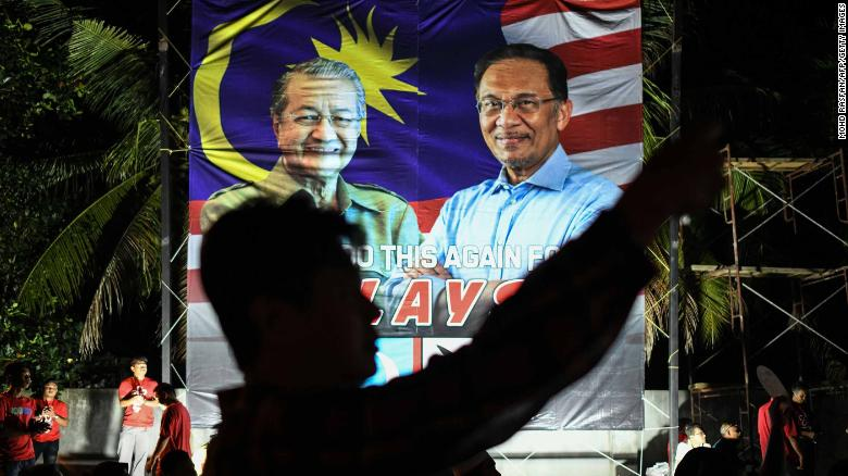 A supporter takes pictures in front of a banner showing former Malaysian Prime Minister Mahathir Mohamad  and Anwar Ibrahim during a rally before the election.
