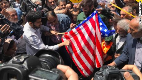 Protesters prepare to burn a US flag at a demonstration in Tehran.