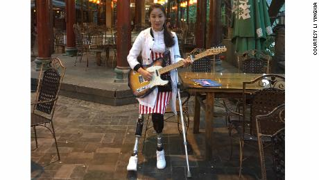 Li Yingxia, Sichuan earthquake survivor, on her artificial limbs with her guitar prior to one of her public singing events.