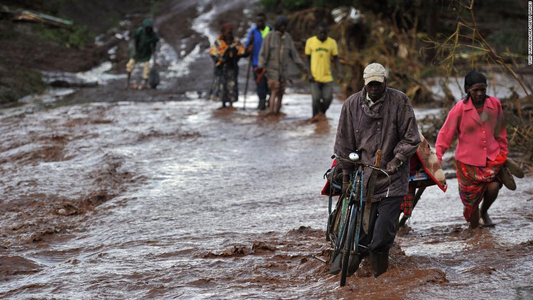 Villagers in Solai, Kenya, cross floodwaters on Thursday, May 10, a day after the Patel Dam burst following weeks of torrential rain. At least 45 people have died, officials said, after homes in the community were swept away. Dozens of people remain missing.