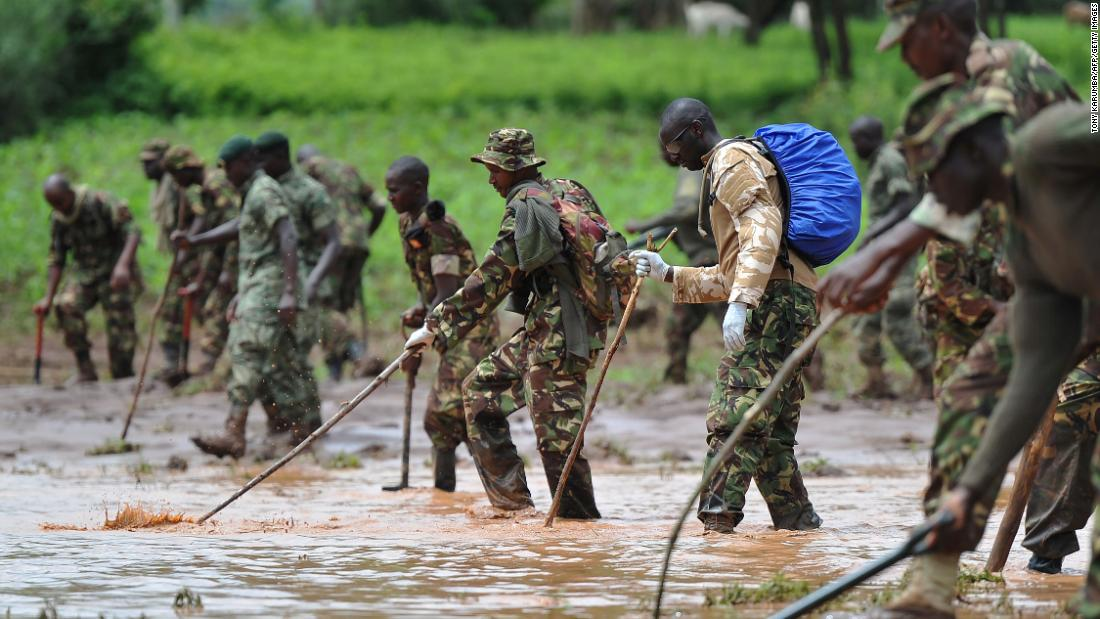 Kenyan soldiers search through mud and debris on Friday, May 11.