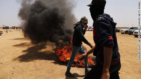 Palestinians burn tires near the border fence with Israel.