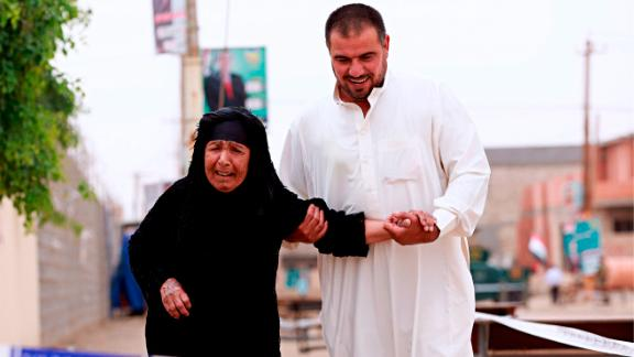 An Iraqi elderly woman is helped by her son as she prepares to casts her ballot in the country's parliamentary elections in Ramadi, Iraq, Saturday, May 12, 2018.