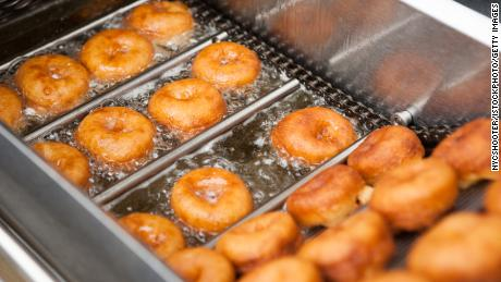 Deep frying doughnut machine close up