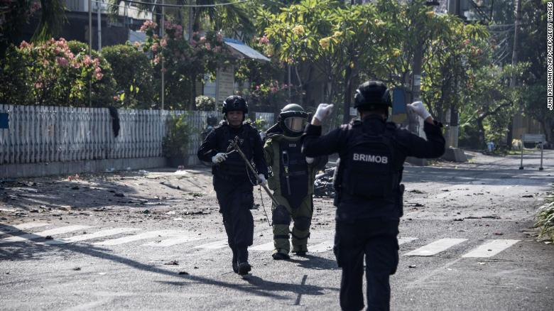 Indonesian bomb squad members examine the site following a suicide bombing outside a church in Surabaya early Sunday.