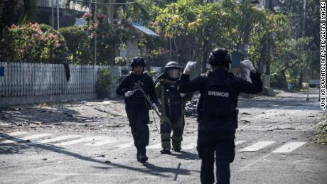 Indonesian bomb squade examine the site following a suicide bomb outside a church in Surabaya on May 13, 2018. - At least two people were killed and 13 others injured in bomb attacks, including a suicide blast, targeting churches in Indonesia's second biggest city Surabaya, police said. (Photo by JUNI KRISWANTO / AFP)        (Photo credit should read JUNI KRISWANTO/AFP/Getty Images)