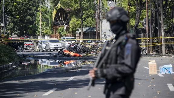 An Indonesian anti-terror policeman stands guard at the blast site following a suicide bomb outside a church in Surabaya on May 13, 2018. - A wave of blasts including a suicide bombing struck outside churches in Indonesia, killing at least six and wounding dozens of others, police said, the latest assault on a religious minority in the world's biggest Muslim-majority country. (Photo by JUNI KRISWANTO / AFP)        (Photo credit should read JUNI KRISWANTO/AFP/Getty Images)