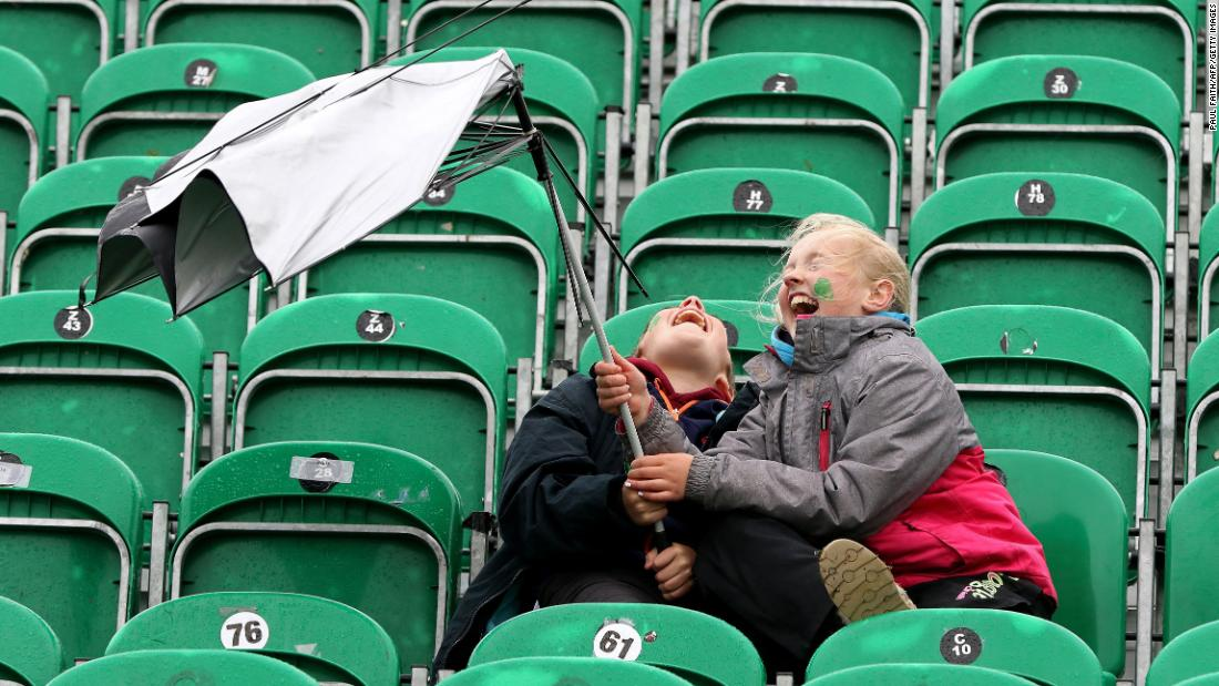 Twelve-year-old Aran Cavanagh, left, and his sister Joise, 11, battle with their umbrella as wind and rain sweep across Malahide Cricket Club in Dublin as the start of play is delayed on the first day of the test match between Ireland and Pakistan on Friday, May 11.