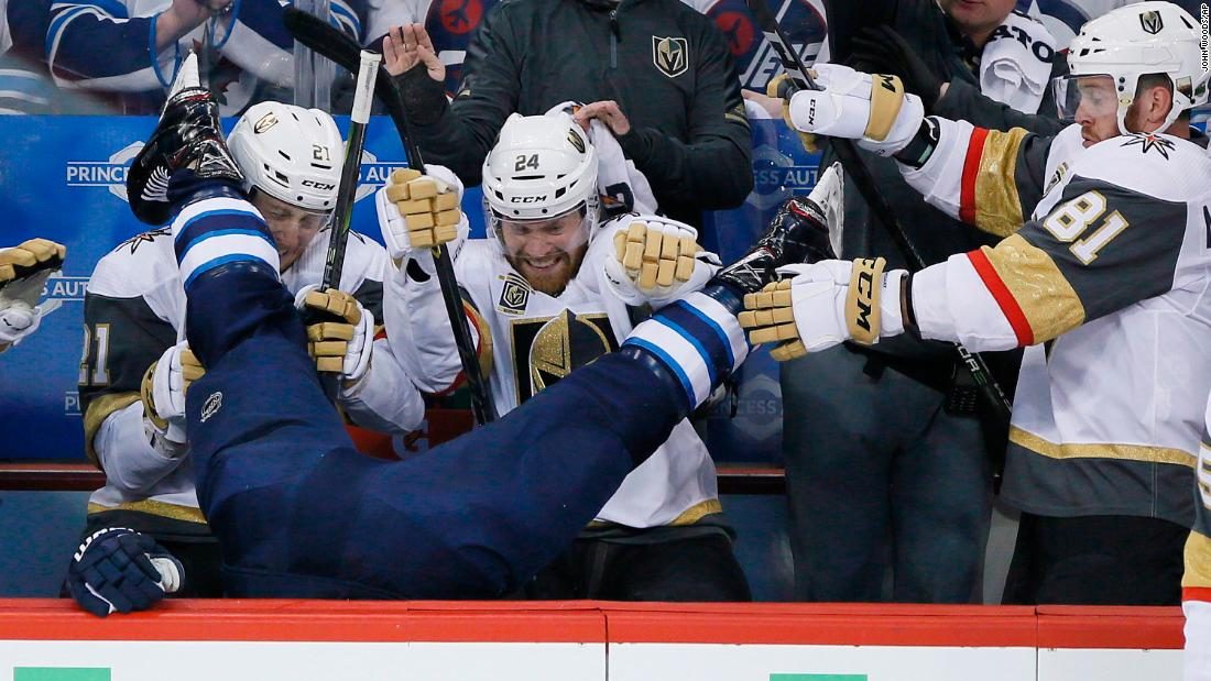 Winnipeg Jets' Blake Wheeler gets dumped over the boards by Vegas Golden Knights' Ryan Reaves, not seen, in front of Cody Eakin (21), Oscar Lindberg (24) and Jonathan Marchessault (81) during the first period of Game 1 of the NHL hockey playoffs Western Conference Final on Saturday, May 12, in Winnipeg, Manitoba.