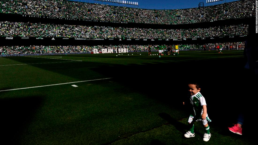 A child runs before the Spanish league football match between Real Betis and Sevilla at the Benito Villamarin stadium in Sevilla, Spain, on Saturday, May 12.