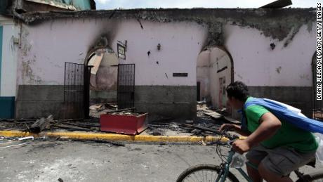 A young man passes by a burned building, in Masaya, Nicaragua on May 13, 2018. - Nicaragua's army on Saturday called for an end to violence in the country and distanced itself from President Daniel Ortega, saying it was not repressing anyone for taking part in anti-government protests.  The wave of unrest against Nicaraguan President Daniel Ortega which broke out in mid-April was triggered by an aborted attempt to reform the near-bankrupt social security system, but quickly expanded to include a wave of grievances against him, including claims of corruption and repression (Photo by DIANA ULLOA / AFP)        (Photo credit should read DIANA ULLOA/AFP/Getty Images)