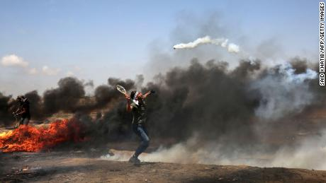 A demonstrator uses a racket to return a tear gas canister fired by Israeli troops during clashes at the Gaza border on Friday, May 11.
