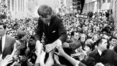 Senator Robert Kennedy is surrounded by hundreds of people as he leans down to shake hands during a campaign appearance at a street corner in central Philadelphia, April 2, 1968. (AP Photo/Warren M. Winterbottom)