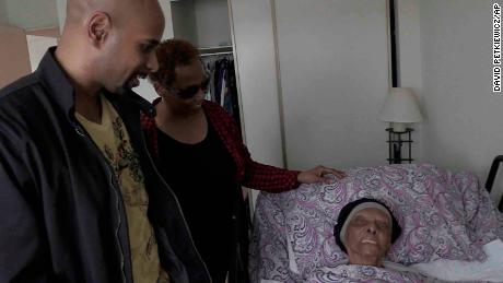 In this May 11 frame from video, family members stop by to visit with Lessie Brown, who is 113, in Cleveland Heights, Ohio.