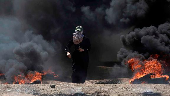 A Palestinian woman walks through black smoke from burning tires during a protest in Gaza on Monday.