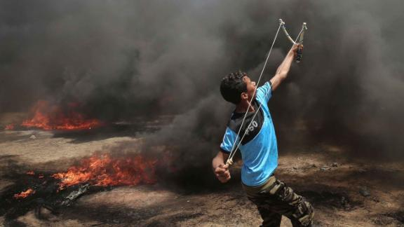 A Palestinian man uses a slingshot during clashes with Israeli forces along the border with the Gaza strip east of Khan Yunis on May 14, 2018, as Palestinians protest over the inauguration of the US embassy following its controversial move to Jerusalem. (Photo by SAID KHATIB / AFP)        (Photo credit should read SAID KHATIB/AFP/Getty Images)