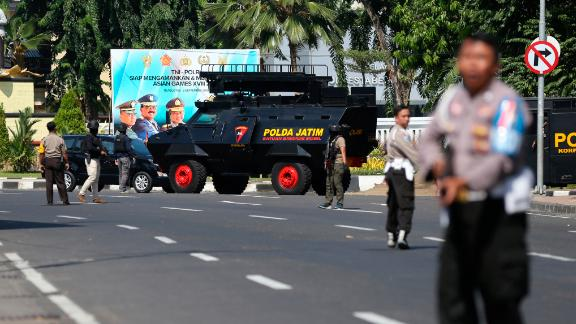 Officers block a road following an attack at the local police headquarters in Surabaya, East Java, Indonesia.