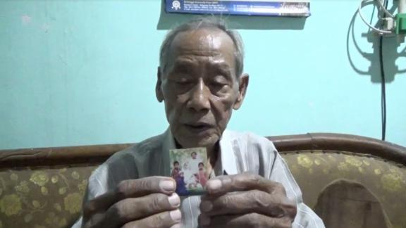 Raden Doddy Oesodo, Dita Oepriarto's father, holds a family photo.