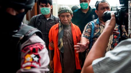 Indonesian armed police escort Indonesian radical cleric Aman Abdurrahman (C) into the South Jakarta courtroom in Jakarta on February 15, 2018.
