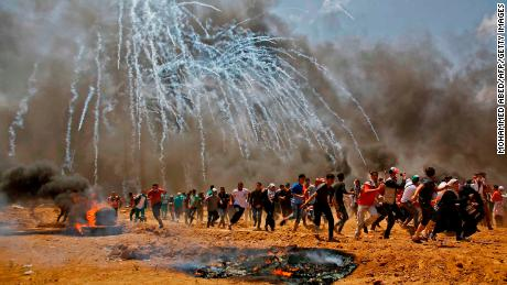 Palestinians run for cover from tear gas during clashes at the fence separating Gaza and Israel.