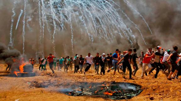 Palestinian protesters run for cover from tear gas in Gaza on May 14, 2018,