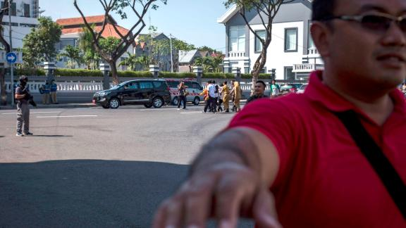 Surabaya's mayor Tri Risma Harini being evacuated away as Indonesian police stand guard outside the Surabaya police station following another explosion.
