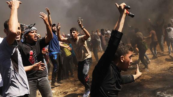 Palestinians rush to the border fence with Israel as mass protests take place on May 14 in Gaza City.