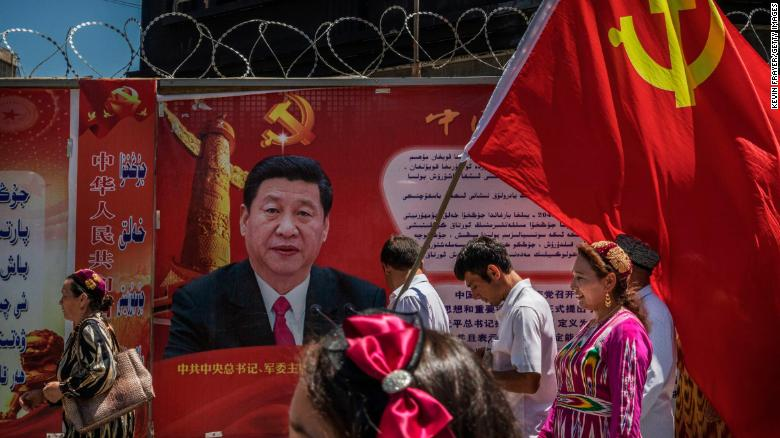 Ethnic Uyghur members of the Communist Party of China carry a flag past a billboard of Chinese President Xi Jinping on June 30, 2017 in Xinjiang province, China.