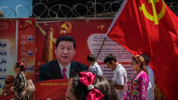 KASHGAR, CHINA - JUNE 30: Ethnic Uyghur members of the Communist Party of China carry a flag past a billboard of Chinese President Xi Jinping as they take part in an organized tour on June 30, 2017 in the old town of Kashgar, in the far western Xinjiang province, China. Kashgar has long been considered the cultural heart of Xinjiang for the province's nearly 10 million Muslim Uyghurs. At an historic crossroads linking China  to Asia, the Middle East, and Europe, the city has  changed under Chinese rule with government development, unofficial Han Chinese settlement to the western province, and restrictions imposed by the Communist Party. Beijing says it regards Kashgar's development as an improvement to the local economy, but many Uyghurs consider it a threat that is eroding their language, traditions, and cultural identity.  The friction has fuelled a separatist movement that has sometimes turned violent, triggering a crackdown on what China's government considers 'terrorist acts' by religious extremists.  Tension has increased with stepped up security in the city and the enforcement of measures including restrictions at mosques. (Photo by Kevin Frayer/Getty Images)