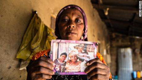 Rebecca Sharibu holds up a photograph that shows her daughter Leah, (left). Leah was kidnapped in February 2018 from her school in the town of Dapchi in northern Nigeria by Boko Haram. Photo by Chika Oduah. April 2018.