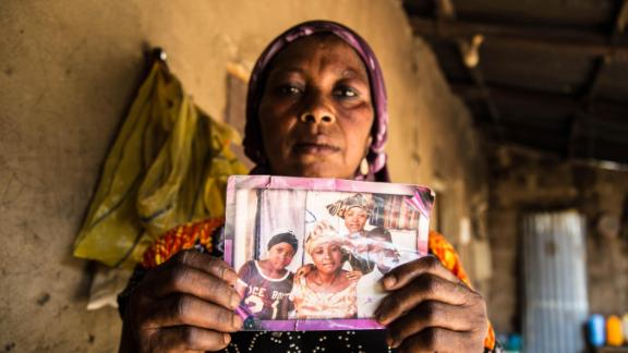 Rebecca Sharibu, 45, holds up a photograph that shows her daughter Leah, seated on the left in a black shirt. Leah was kidnapped in February 2018 from her school in the town of Dapchi in northern Nigeria by Boko Haram. Photo by Chika Oduah.