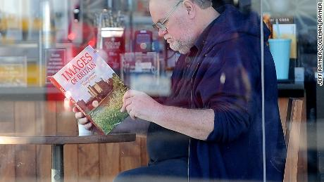 Meghan Markle's father Thomas Markle reads a book about Britain in an allegedly staged photo.