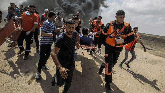 GAZA CITY, GAZA - MAY 14: Medical units carry away a wounded Palestinian shot by Israeli forces during a protest on the border fence separating Israel and Gaza on May 14, 2018 in a camp east of Gaza City, Gaza. (Photo by Marcus Yam/Los Angeles Times via Getty Images)