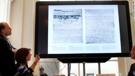 A video shows the text underneath two taped off pages from Anne Frank's diary during a press conference at The Anne Frank Foundation's office in Amsterdam, Netherlands, Tuesday, May 15, 2018. Left standing is the foundation's director Ronald Leopold. Researchers have used digital photo editing techniques to uncover the text on two pages from Anne Frank's world famous diary that the teenage Jewish diarist had covered with brown masking paper, revealing risque jokes and an explanation of sex and prostitution. (AP Photo/Peter Dejong)